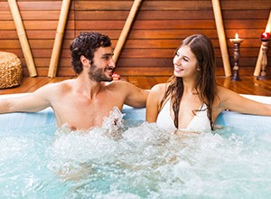 Couple in a hot tub with a wooden background