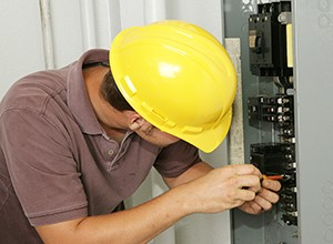 Electrician with yellow hard hat repairing electrical panels