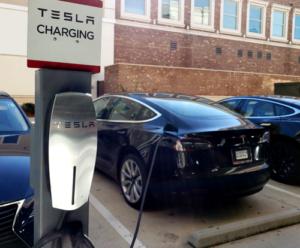 Black Tesla parked while charging