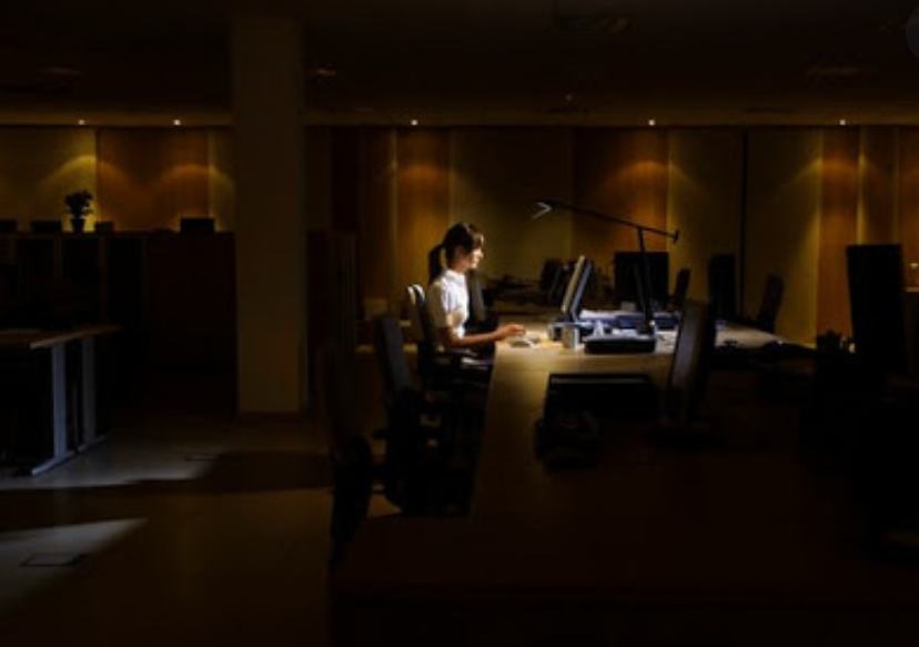 Women working at her desk with dim lighting