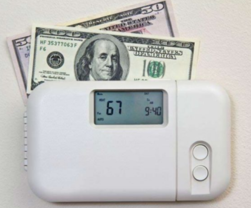 white thermostat with cash behind it